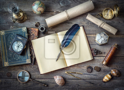 Columbus Day, exploration and nautical theme vintage background. Globe, telescope, lamp, divider, old coins, shell, map, shell, book, compass, hourglass, quill pen on wood desk.