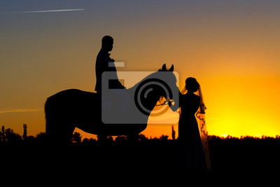 Couple in wedding day with horse silhouette against sunset sky