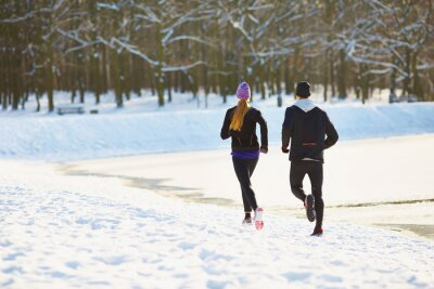 Wall mural Couple running during winter