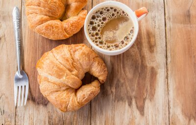 Wall mural Croissant and coffee for breakfast on old wooden table