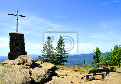 Cross and wooden bench on the summit of a mount Grosser Falkenstein in the National park Bayerische Wald, Germany.