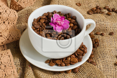 Cup filled with coffee beans and pink flower