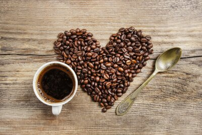 Wall mural Cup of coffee and heart made of coffee beans on wooden table. To