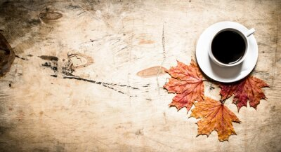 Wall mural Cup of hot coffee with autumn leaves.
