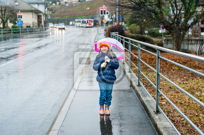 Cute little girl with umbrella in a city on a rainy day