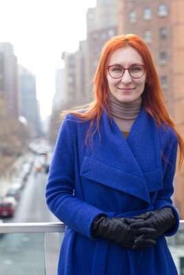 Cute red-haired girl in a blue coat and glasses standing on the background of the big city