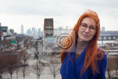Cute red-haired girl in a blue coat and glasses standing on the background of the big city, her hair fluttering in the wind