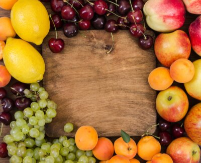 Different fruits around wooden cutting board