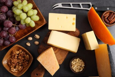 Different types of cheese on a wooden board and other snacks like nuts, fruits.