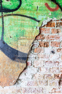 Dirty concrete wall with graffiti and big crack