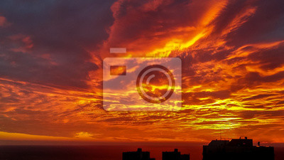 Dramatic bloody red orange colored sky sunset above silhouette of cityscape buildings Haifa city and Mediterranean Sea