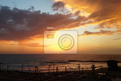 Dramatic colored sky sunset above Haifa city coastline Mediterranean Sea, Israel. Silhouettes of people in the water and on the beach