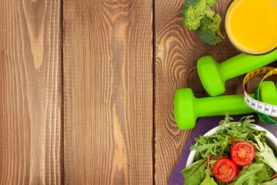 Wall mural Dumbells, tape measure and healthy food. Fitness and health