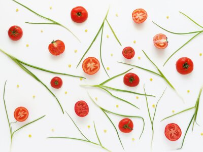 Wall mural Eating a pattern of fresh tomatoes and green onions. Vegetable food background. Cut tomatoes on a white background.