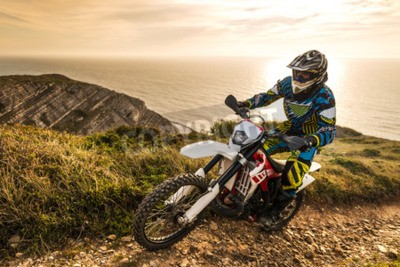 Wall mural Enduro rider climbing a steep slope against a beautiful sunset on a seascape