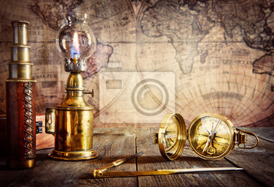 Exploration and nautical theme grunge background. Compass, telescope, sextant, coin, divider on wood desk.