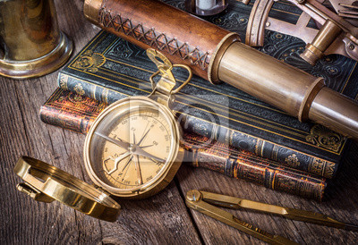 Exploration and nautical theme grunge background. Compass, telescope, sextant, divider and old book on wood desk.