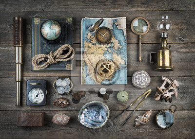 Exploration and nautical theme grunge background. Compass, telescope, sextant, divider, old coins, rope, shell, map, globe, magnifier, hourglass on wood desk. Retro style.