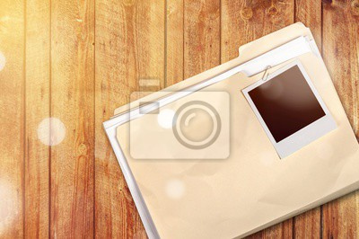 File folder with documents and blank photo in wooden table
