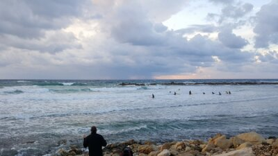 Fisherman rear view is fishing and looking at group of surfers in the sea, evening, sunset, Haifa, Israel
