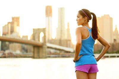 Wall mural Fitness woman runner relaxing after city running