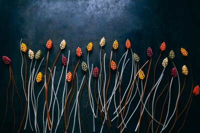 Wall mural flowers composition made out of colorful pasta on the dark  table, topview