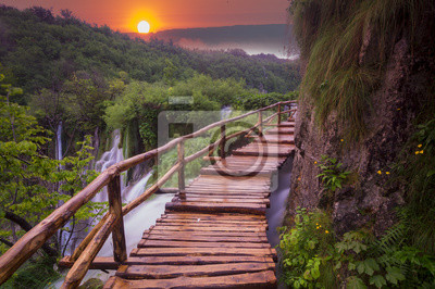 foggy and multicolored dawn over beautiful waterfalls in the park of plitvice lakes in croatia