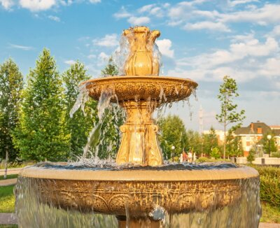 Fountain with pouring water in summer city park