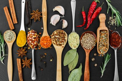 Wall mural Fragrant seasonings and spices on black background.