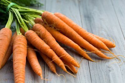 Wall mural Fresh carrots bunch on wooden background