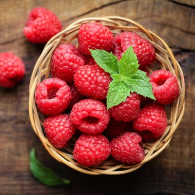 Wall mural Fresh ripe red raspberries in a wicjer bowl on dark rustic wooden background