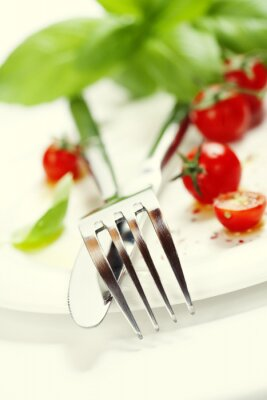 Wall mural fresh tomatoes, knife and fork on a plate