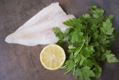 Wall mural Frozen Alaska Pollock fillet with lemon and parsley. Preparation for cooking.
