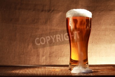 Wall mural Full glass of freshness beer with foam on table against gray canvas background