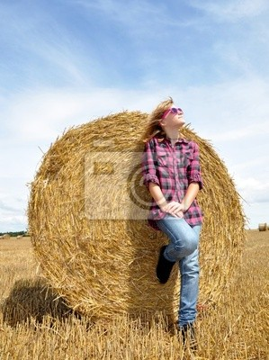 Girl leaning on stack of straw