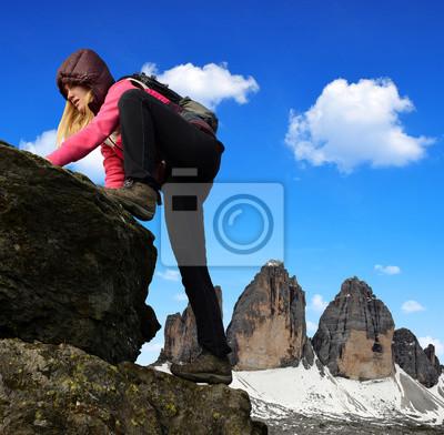 Girl on rock, in the background Tre Cime di Lavaredo - Dolomites, Italy