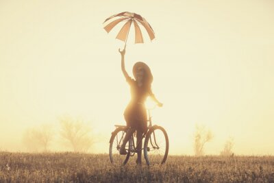 Wall mural Girl with umbrella on a bike in the countryside in sunrise time