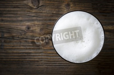 Wall mural Glass of beer foam over wooden table