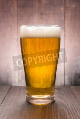 Wall mural Glass of beer on the wooden background.