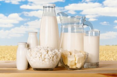 Glass of milk and dairy products on sky background