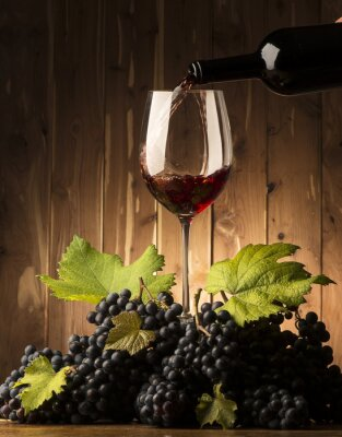 Wall mural Glass with red wine and grapeson the wooden table