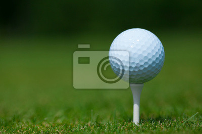Wall mural golf ball on a white tee with a green grass in background
