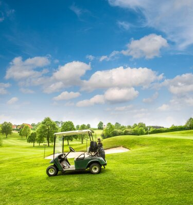 Wall mural Golf cart on a golf course. Green field and cloudy blue sky