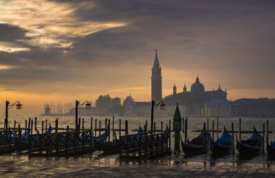 Wall mural Gondolas by Saint Mark square during sunrise with San Giorgio di Maggiore church in the background in Venice Italy