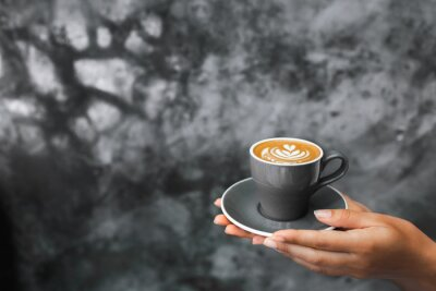 Wall mural Gray cup of fresh cappuccino in woman hands on background of gray concrete cement textured wall. Trendy hipster cafe design.