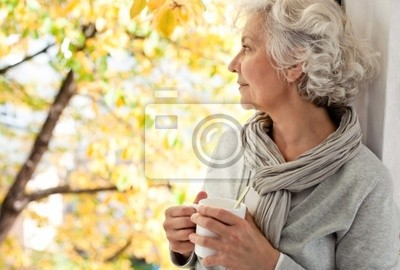 gray-haired, attractive woman enjoys the sunny autumn