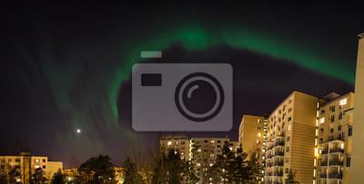 Green aurora borealis over city buildings