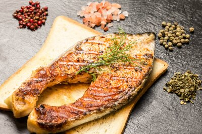 Wall mural grilled salmon fillet over hot bread slice and spices over slate
