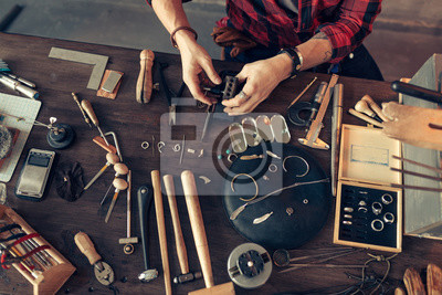 Wall mural guy is sitting at messy desk in the workshop, top view cropped photo