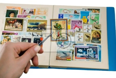 Hand holding postage stamp with a forceps above the album